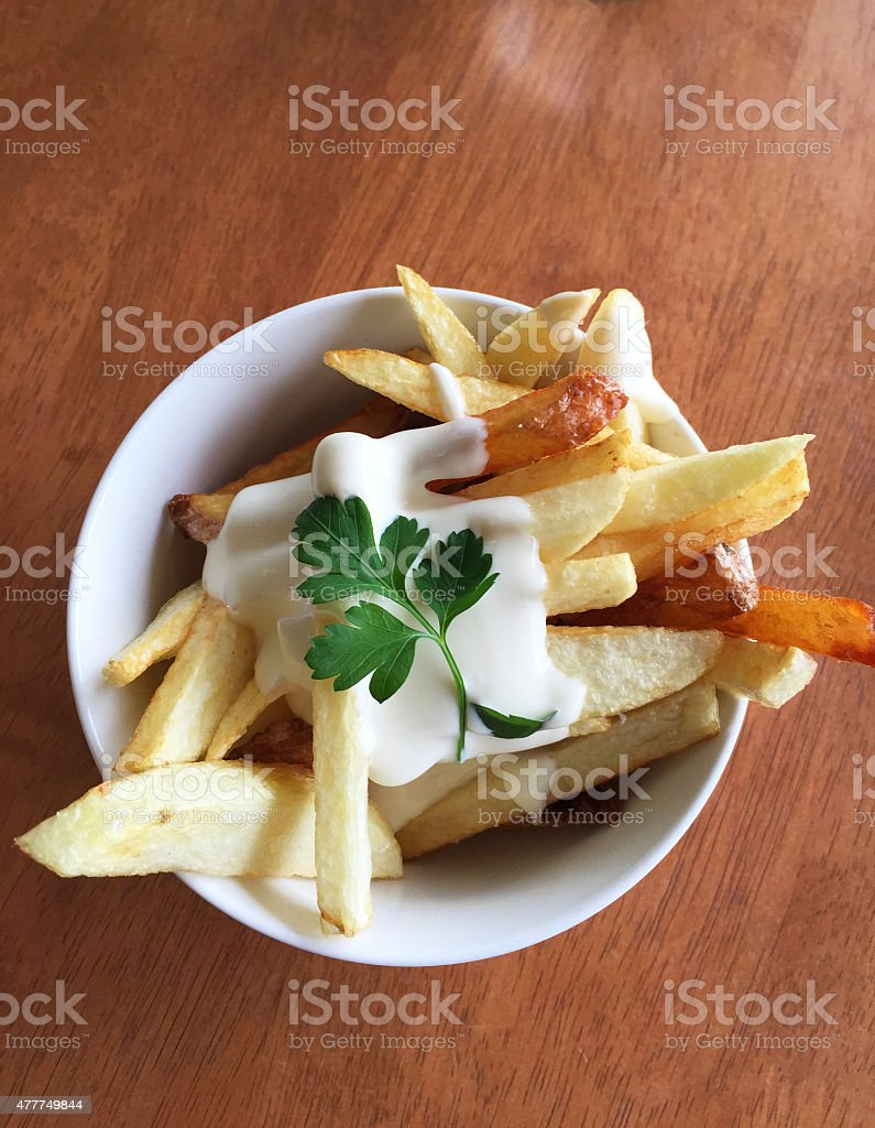hand cut fries with a dollop of aioli and parsley stock photo