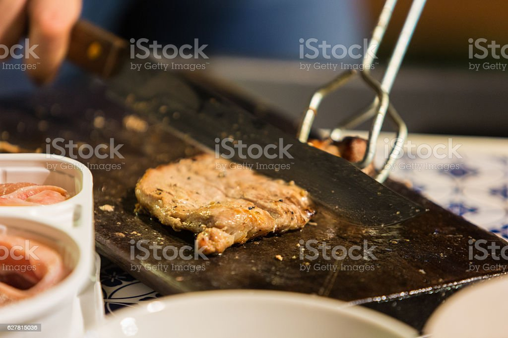 Hand cutting a slice of pork meat on chopping wood. stock photo