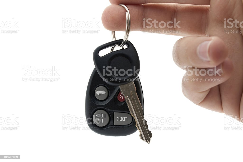 Hand dangling car keys and locking remote on white stock photo