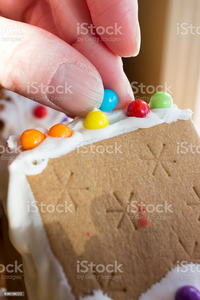 Hand decorating gingerbread house stock photo