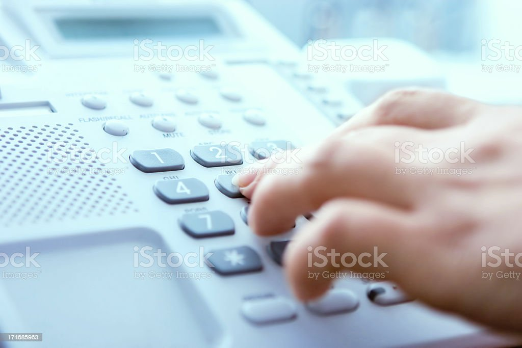 A hand dialing on a landline phone stock photo
