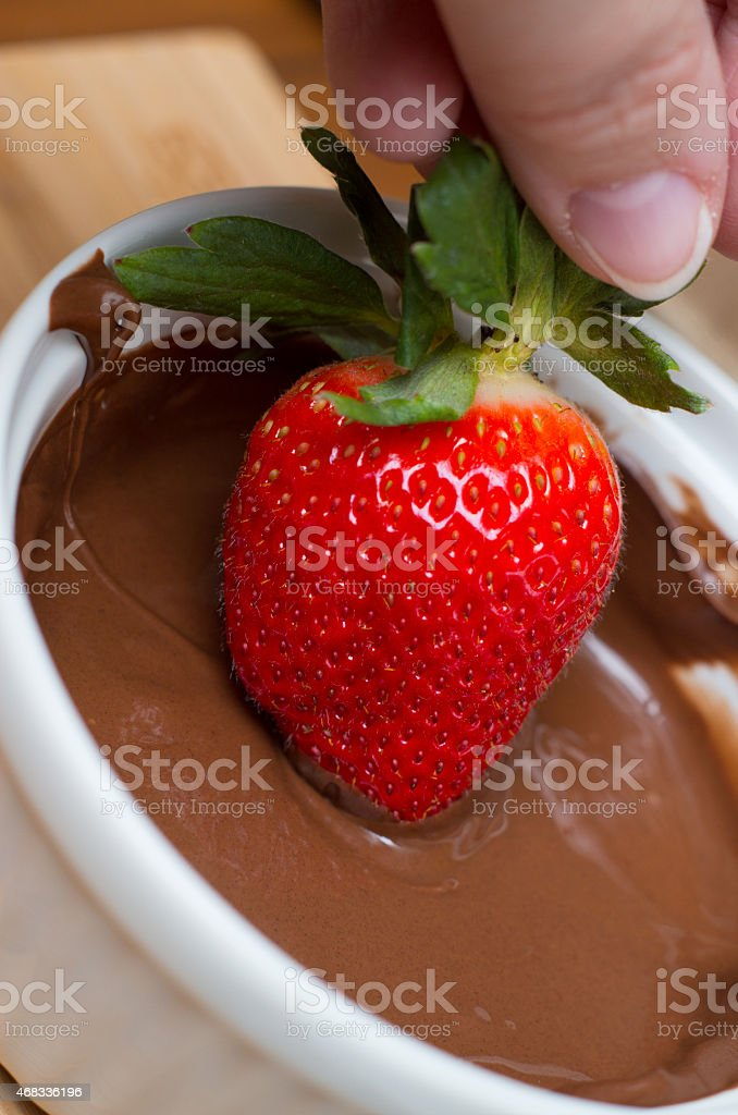 hand dipping chocolate covered strawberry stock photo