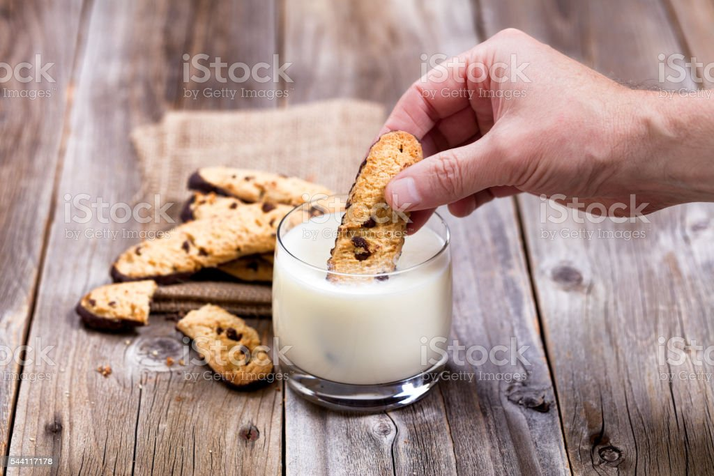 Hand dipping homemade chocolate chip cookies into full glass of stock photo