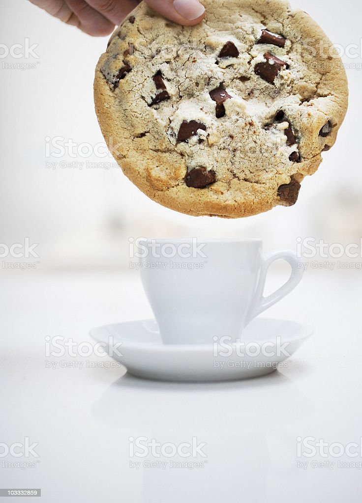 Hand dipping large chocolate chip cookie in small coffee cup stock photo