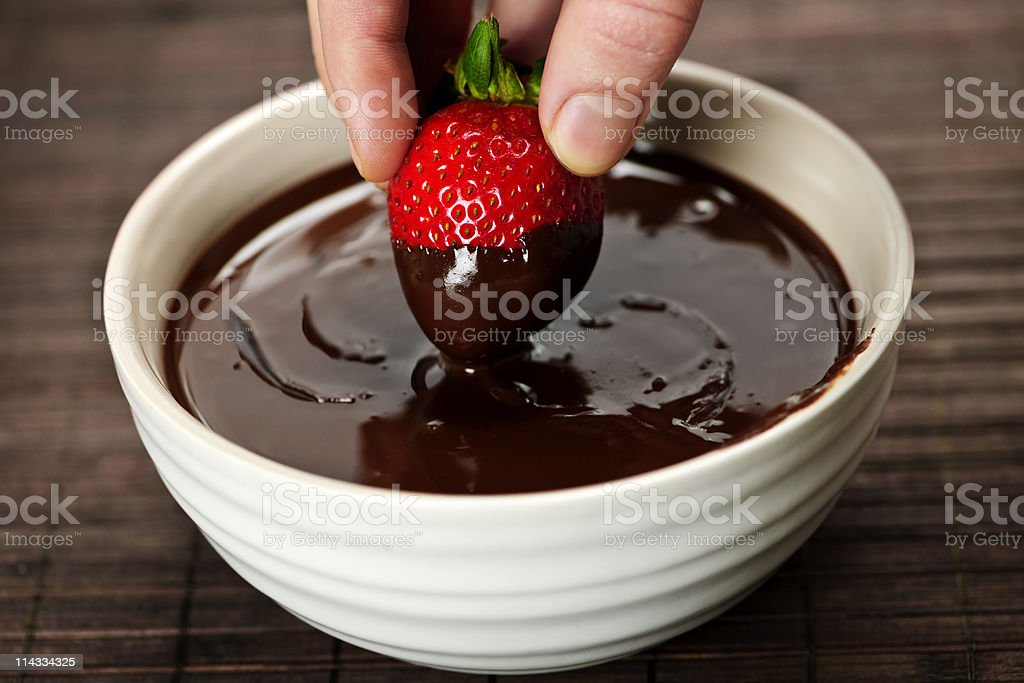 Hand dipping strawberry in chocolate stock photo