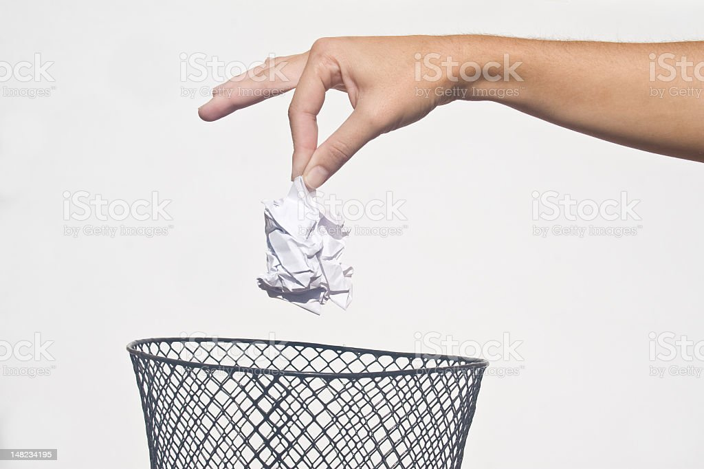 Hand disposing of rubbish in a trash can stock photo