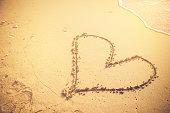 hand draw heart on sand beach valentine concept