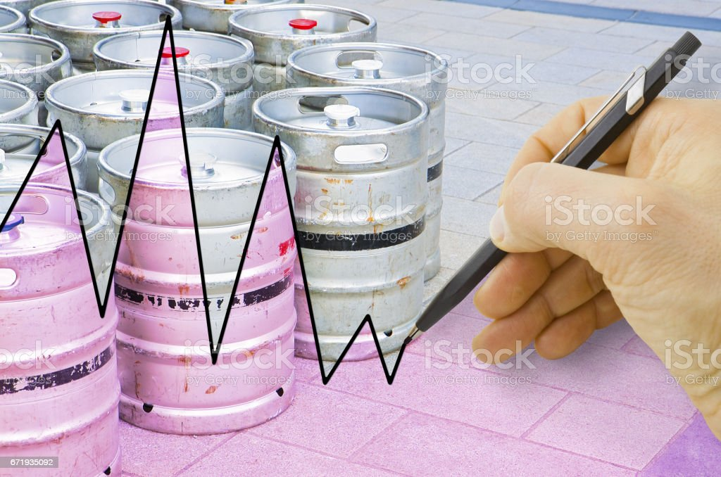 Hand drawing a graph about the trend of beer production with kegs of beer on background stock photo