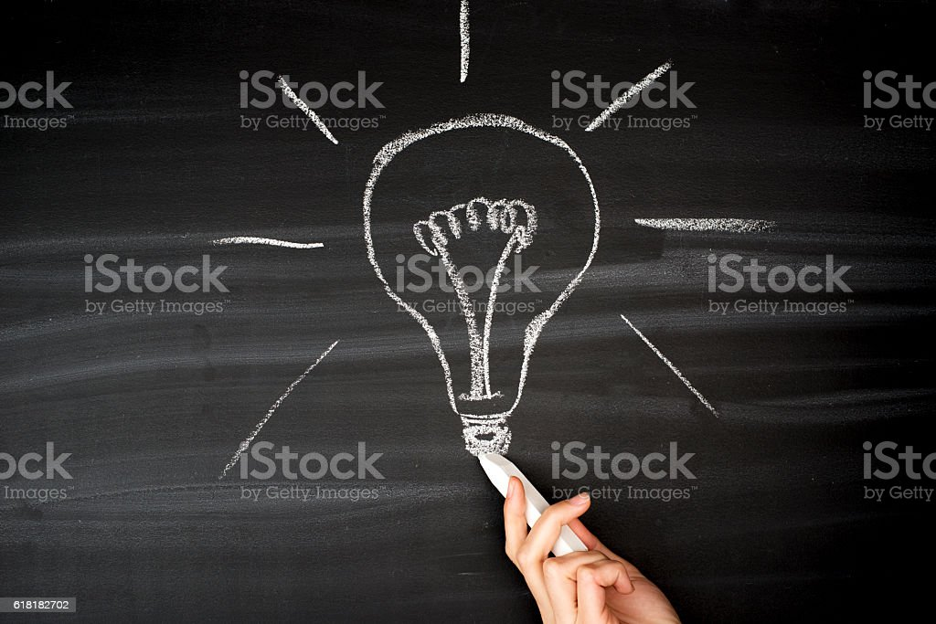 Hand drawing light bulb chalk on a blackboard. stock photo