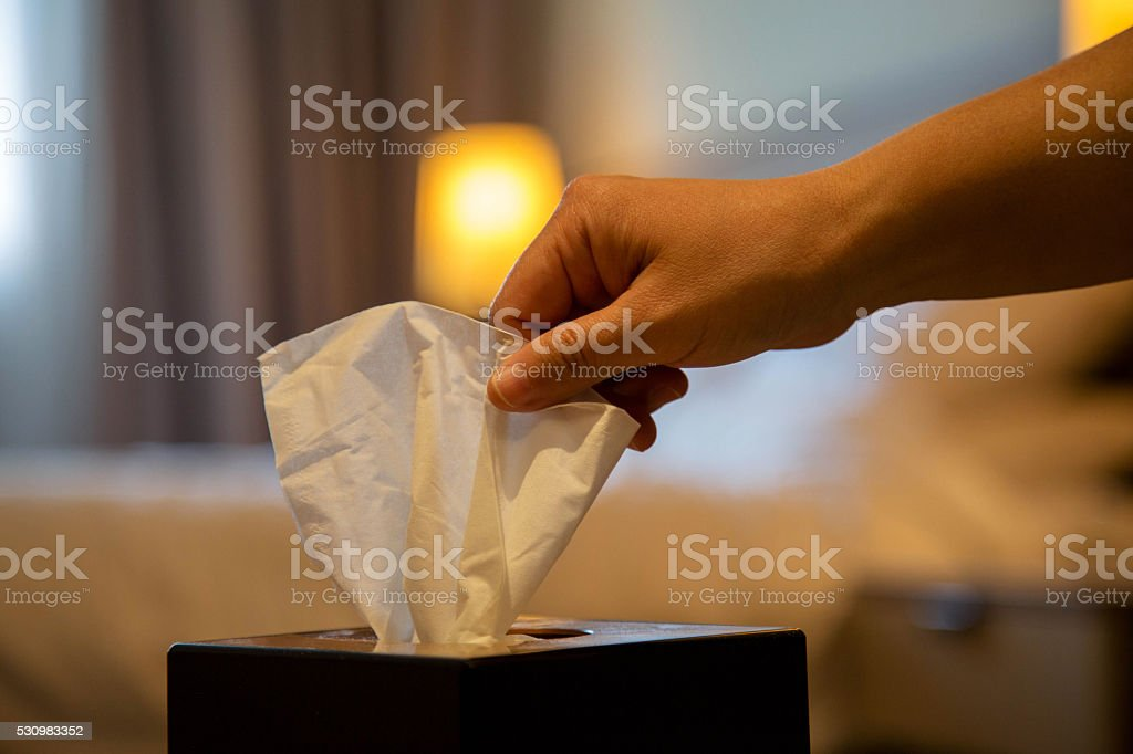 hand drawing tissue from tissue box on table stock photo