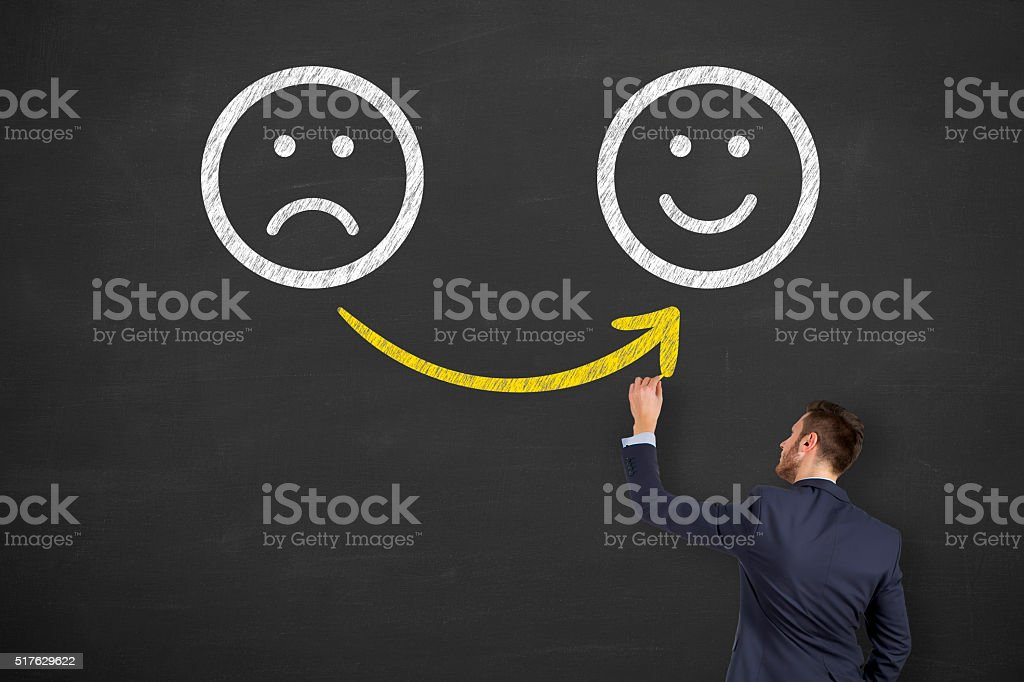 Hand drawing unhappy and happy smileys on blackboard stock photo