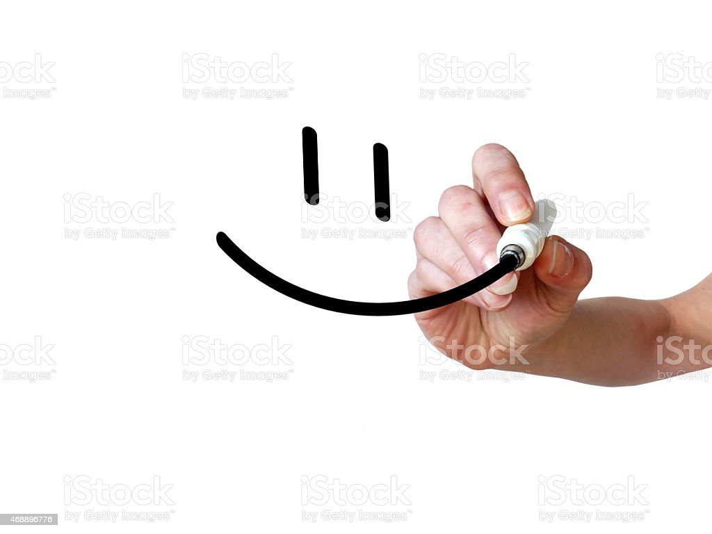 Hand draws smiley with black marker on transparent whiteboard stock photo