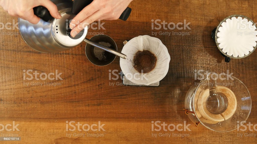 Hand drip coffee , barista pouring water on coffee ground with filter stock photo