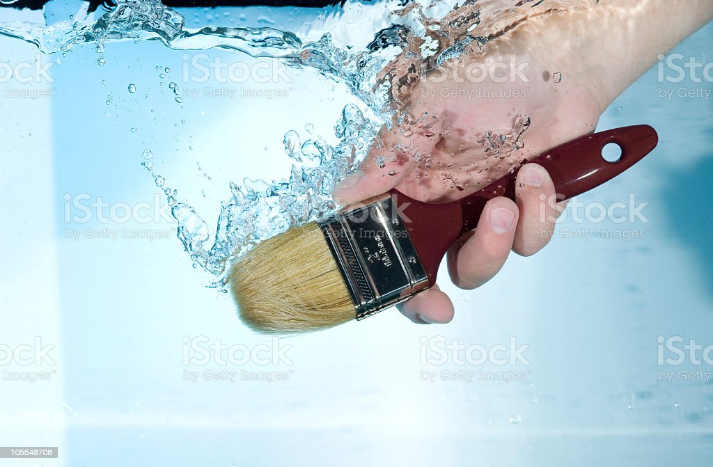 Hand drowning a paint brush in the water stock photo