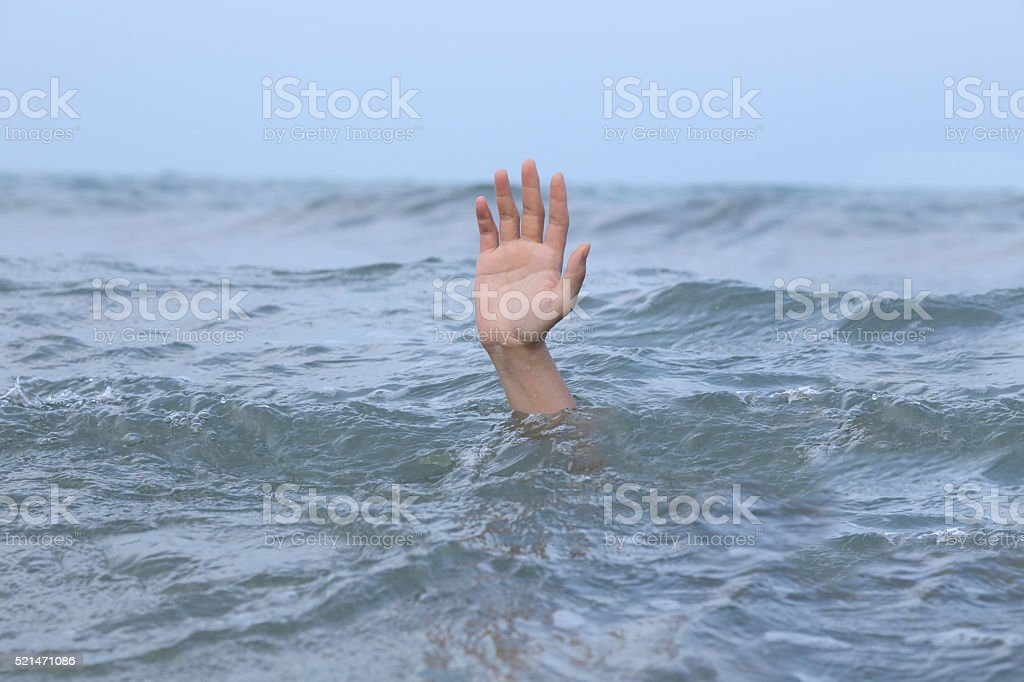 hand drowning in the sea stock photo