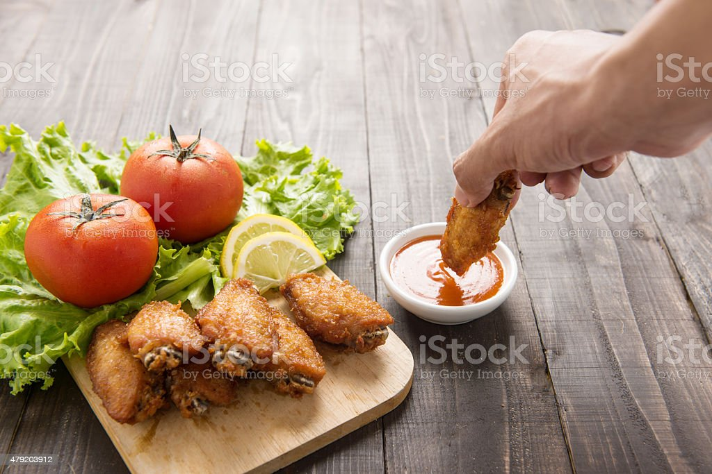 Hand dunk chicken hot wings in dipping sauce on wooden. stock photo