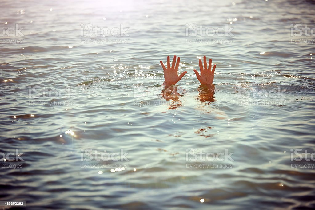 Hand emerges , man drowning stock photo