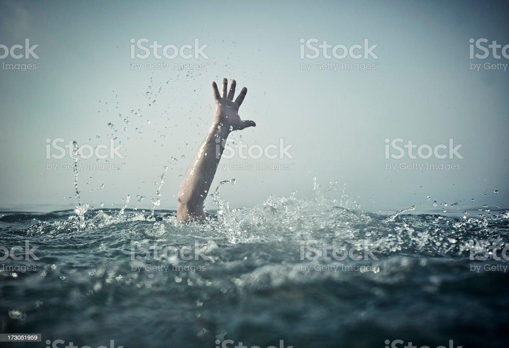 Hand emerges splashing water from below stock photo