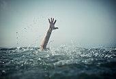 Hand emerges splashing water from below