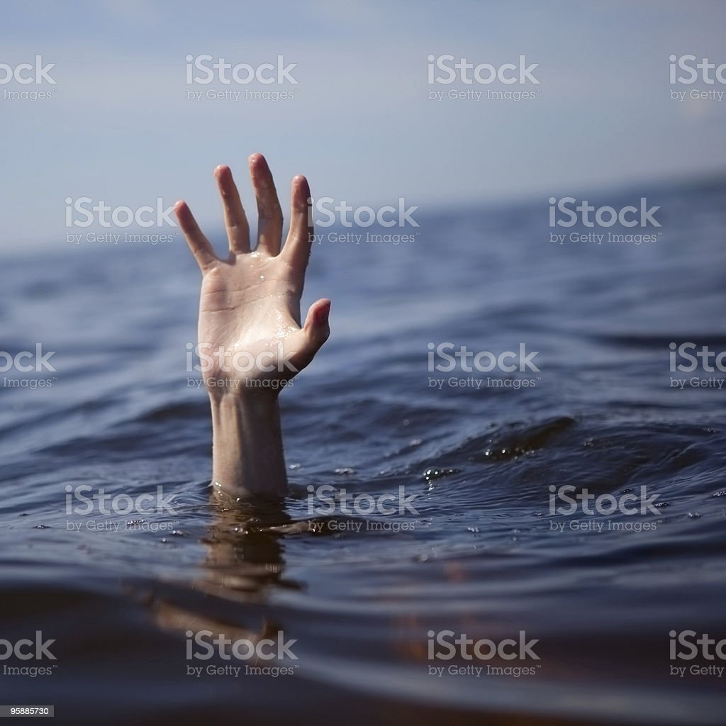 A hand emerging from sea water stock photo