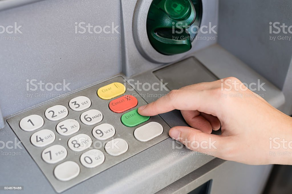 Hand entering personal identification number on ATM dial panel stock photo