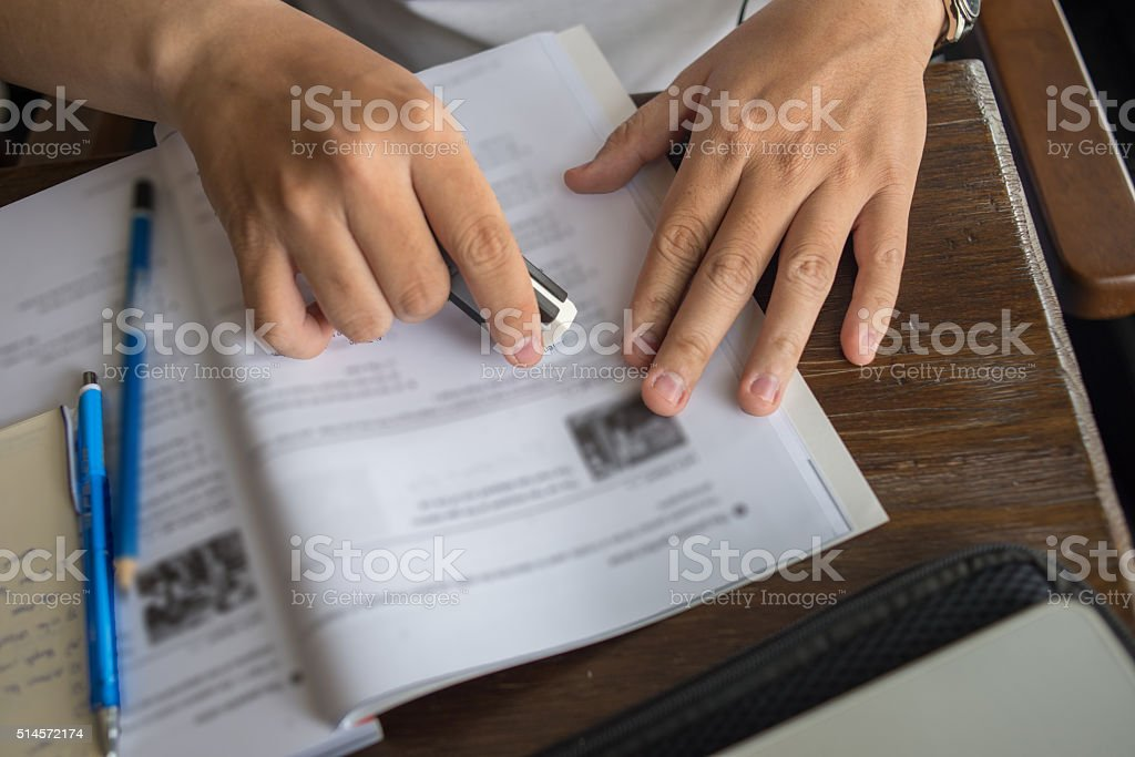 Hand erasing wrong information on the book stock photo