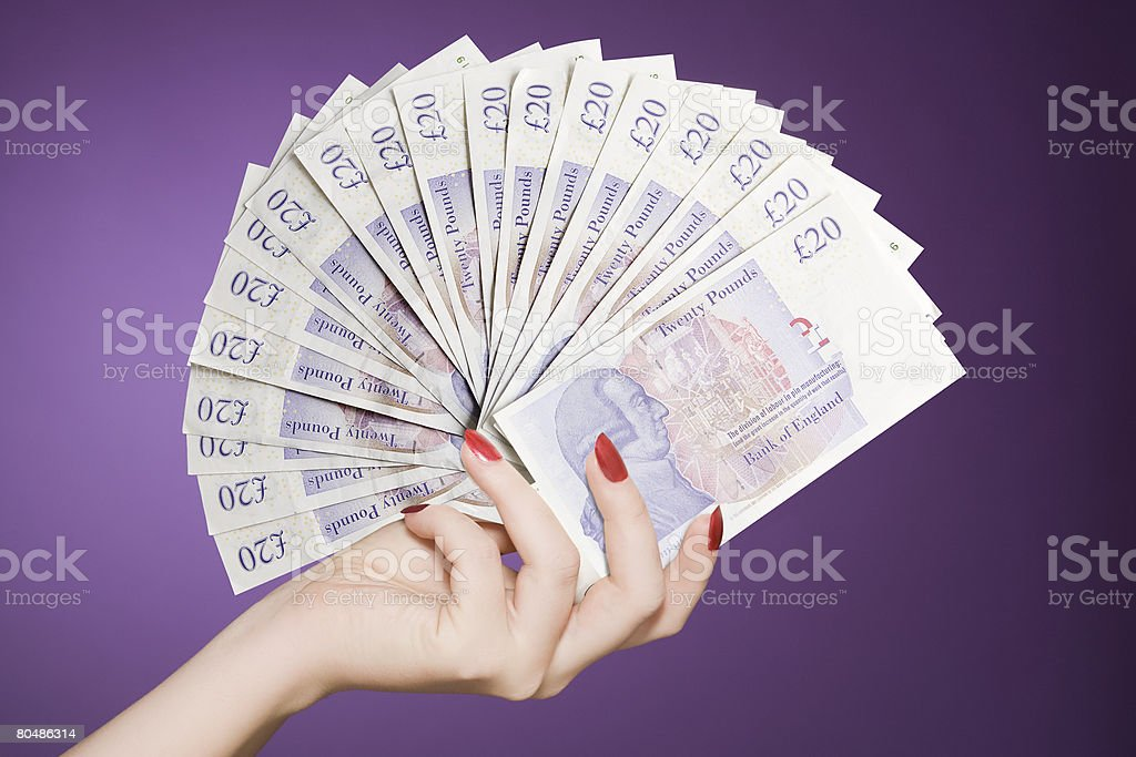 Hand fan of banknotes stock photo