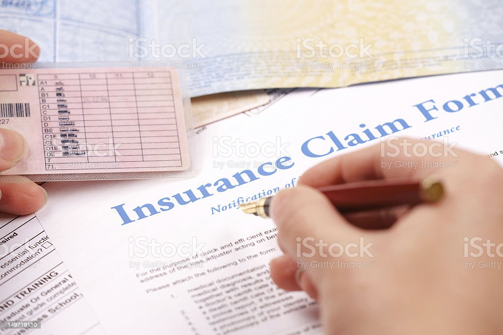 hand filling in insurance claim form royalty-free stock photo