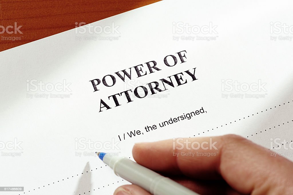 Hand filling in Power of Attorney authorization stock photo