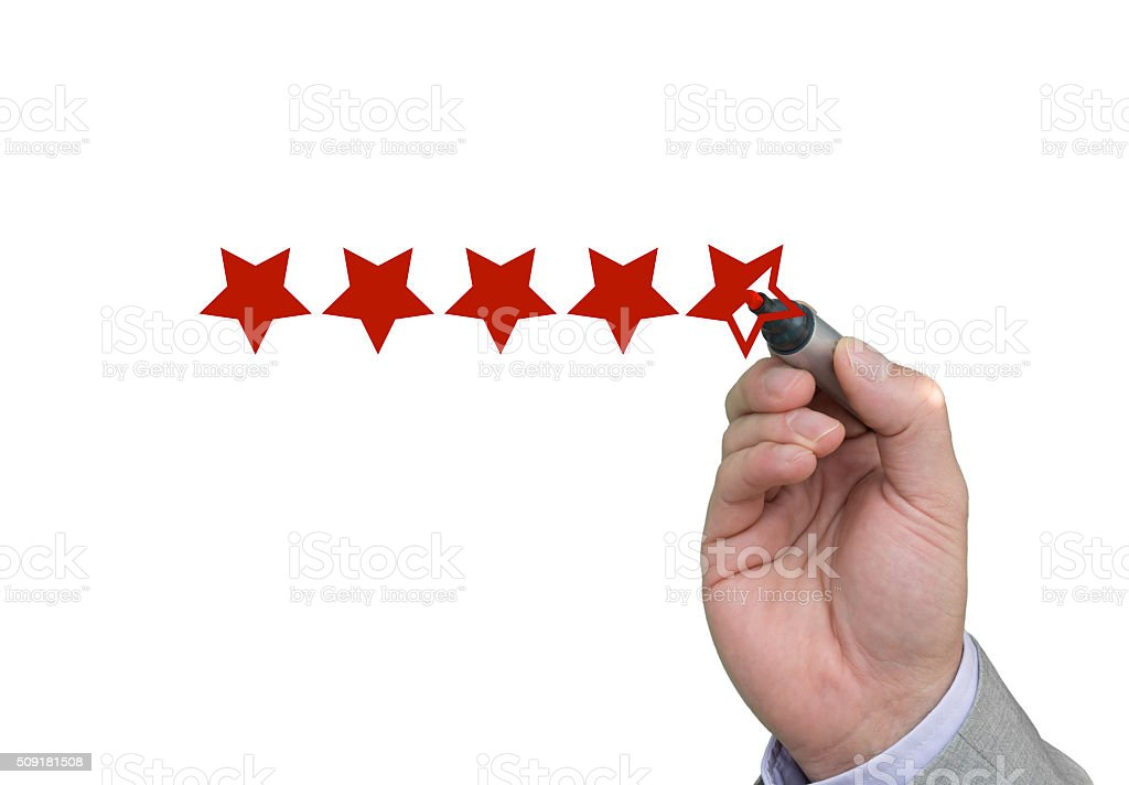 Hand filling out fifth star of performance rating stock photo