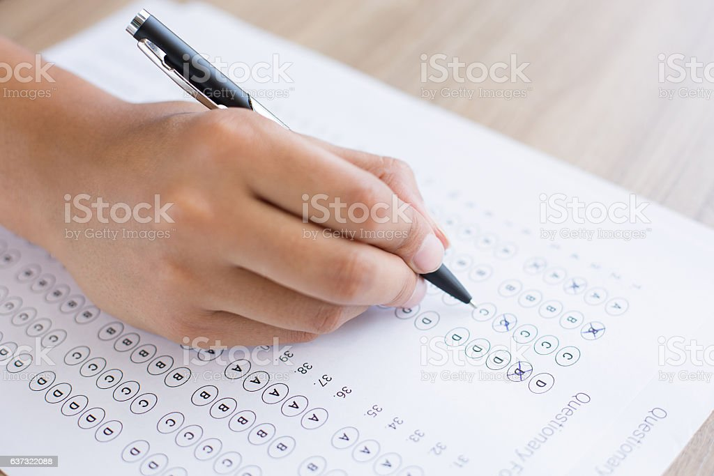 Hand Filling out Quiz Form stock photo