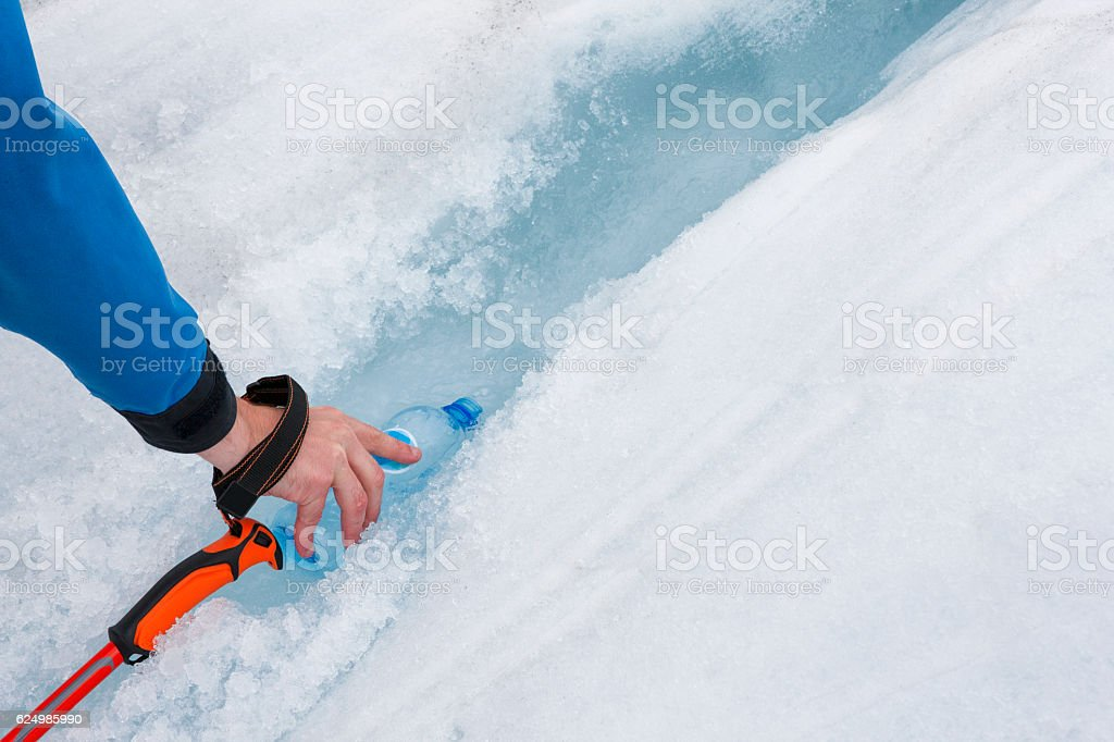 Hand filling water bottle on Franz Josef Glacier, New Zealand stock photo