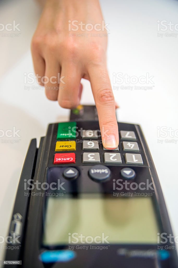 Hand, fingers entering pin with a hand held pin pad. stock photo