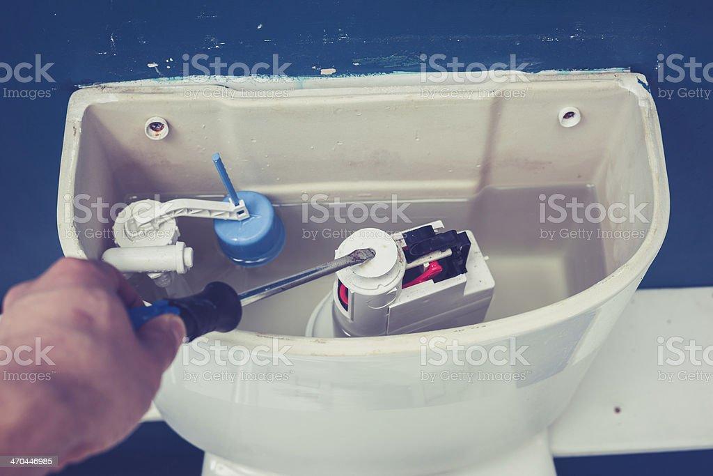 Hand fixing toilet stock photo