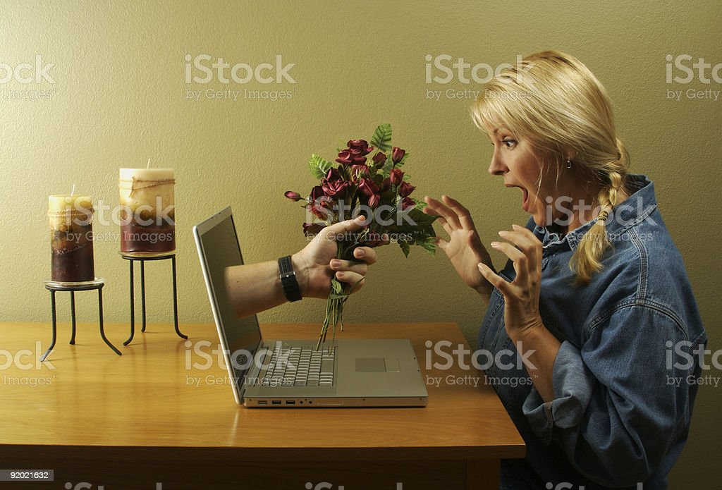 Hand & Flowers Coming Through Laptop Screen stock photo