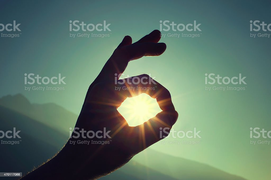 Hand gesture Ok with sun in the background stock photo