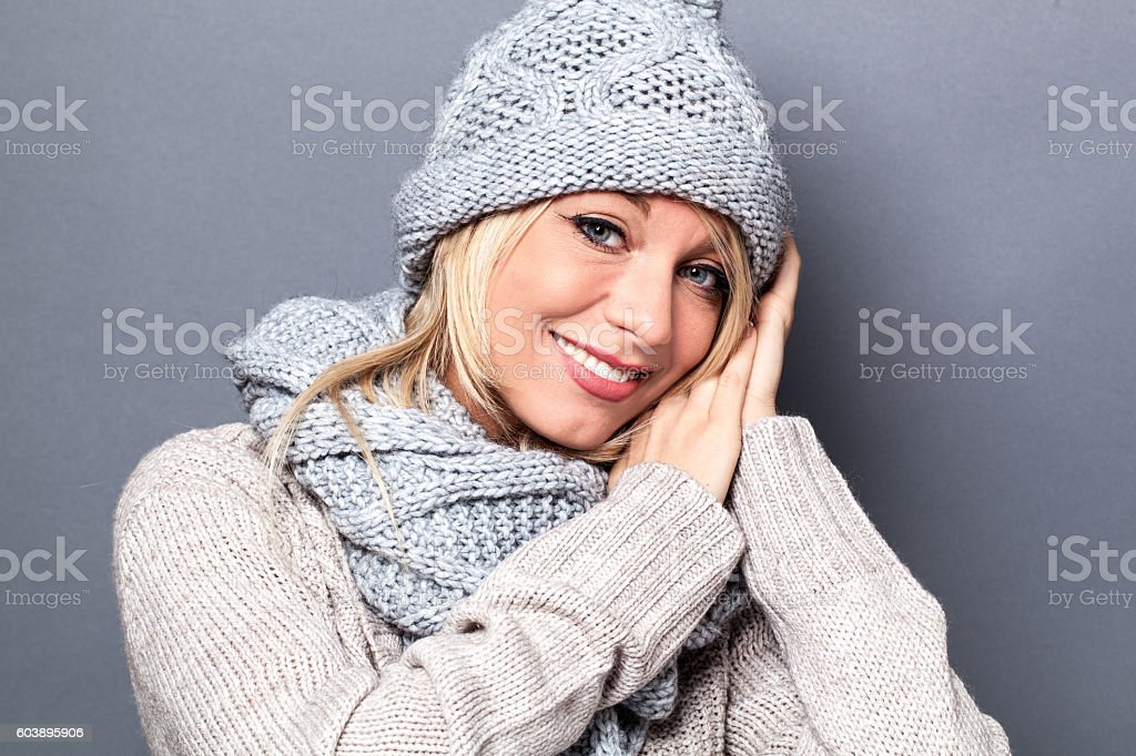 cute young beautiful blond woman using hand gesture to express winter...