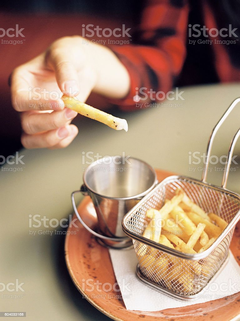 Hand girl with fries dunks in sauce royalty-free stock photo