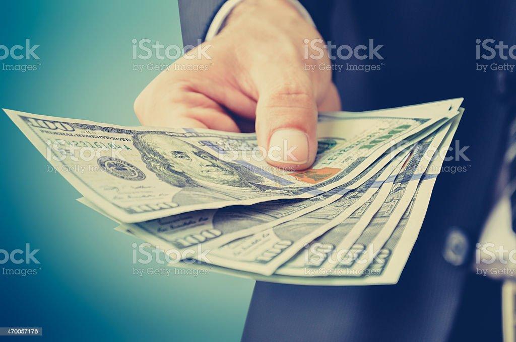 Hand giving money, US dollar (USD) bills - vintage tone stock photo