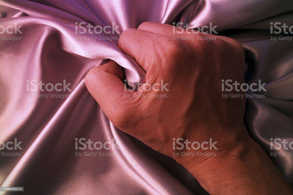 A hand grasps pink silk sheets royalty-free stock photo
