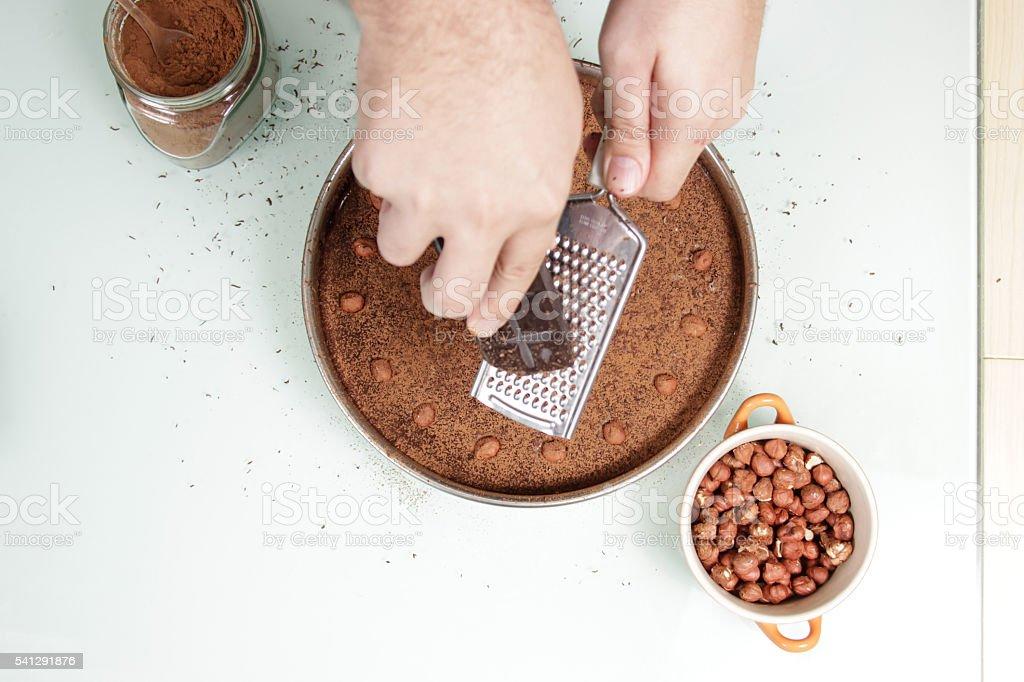 Hand grating chocolate on top of chocolate cake Sacher Sachertor stock photo