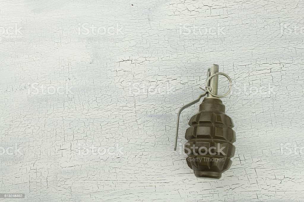 Hand grenade on shadowed, cracked background stock photo