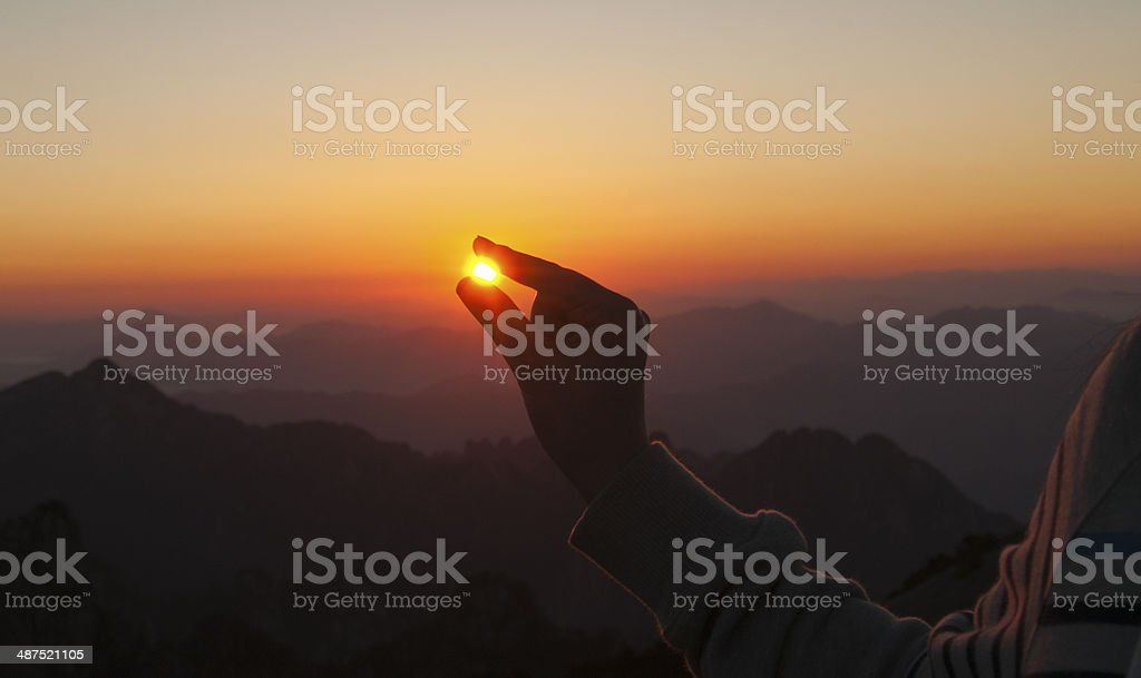 Hand gripping the sun stock photo