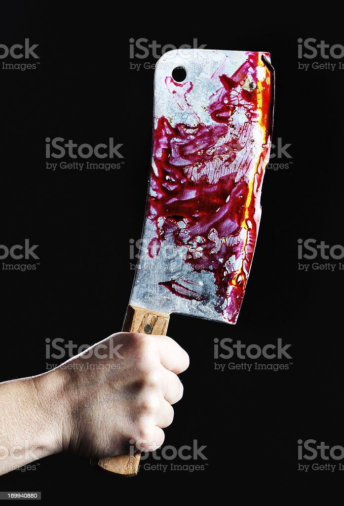 Hand grips gruesome blood-covered meat cleaver: butcher or murderer? stock photo