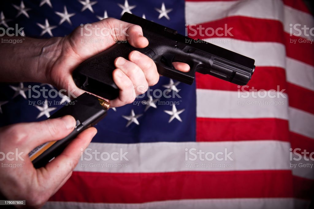 Hand, gun and American flag stock photo