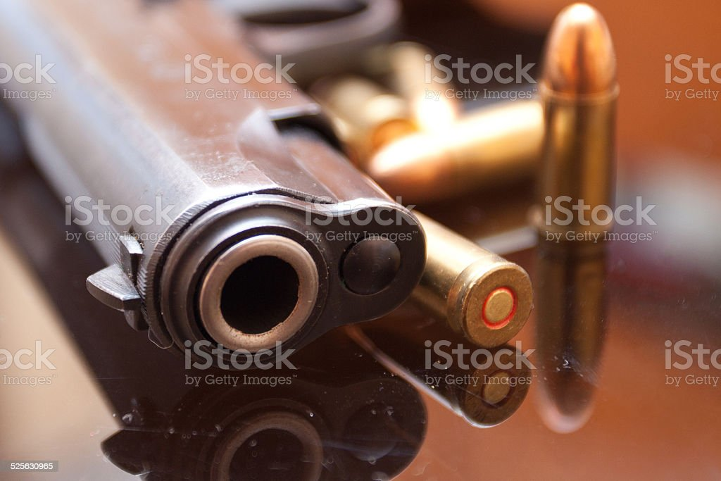 Hand gun with bullets around stock photo