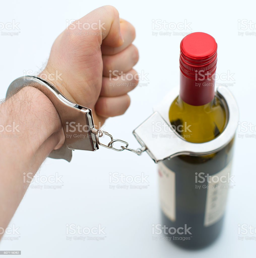 Hand handcuffed to bottle of wine. Alcoholism concept. stock photo