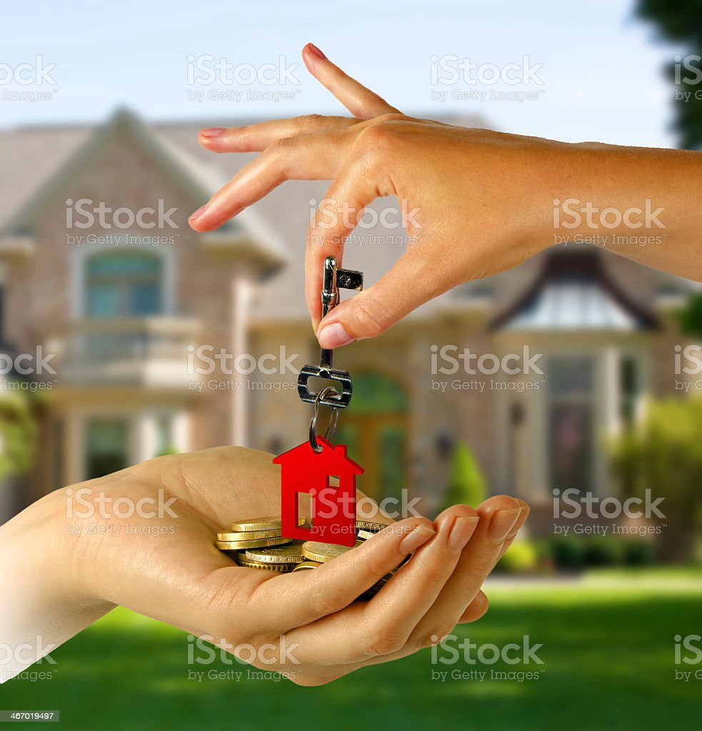 Hand handing over keys with red keychain in front of house stock photo