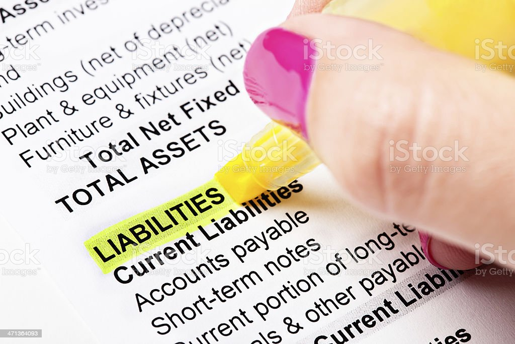 Hand highlights word Liabilities on financial document stock photo