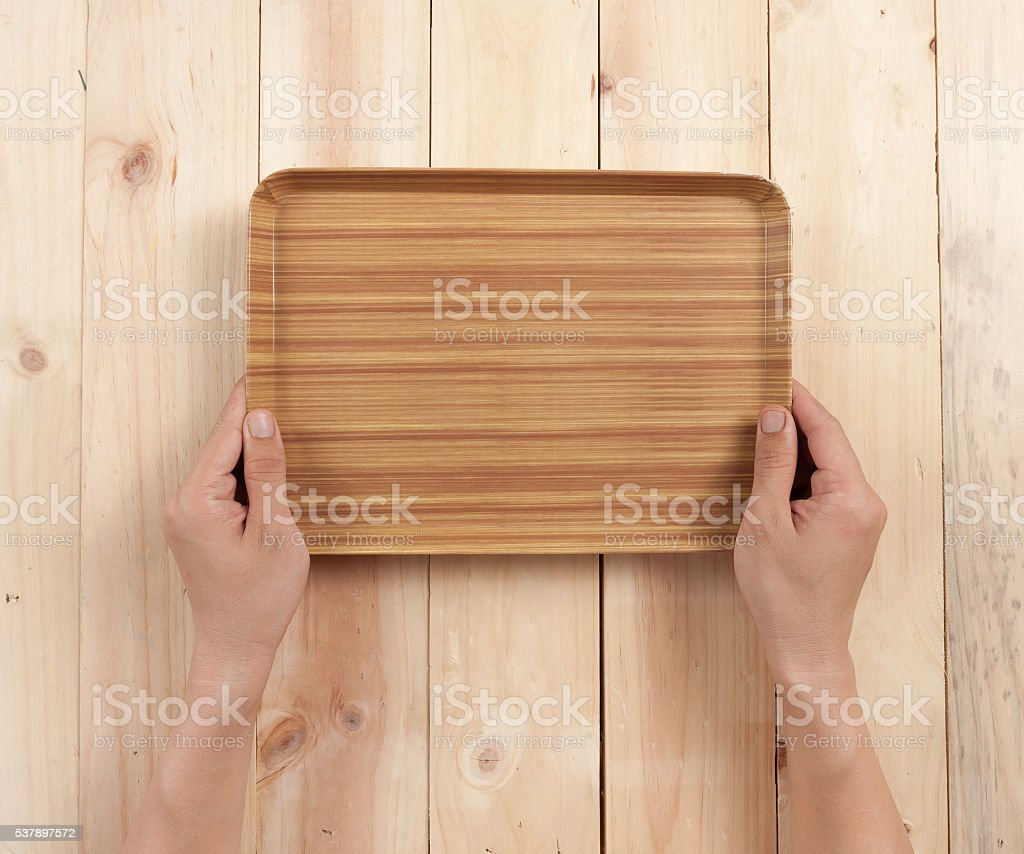 Hand hold a wooden tray on table wood, top view stock photo